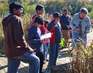 Naturalist points out something in the wetlands to a group of youngsters