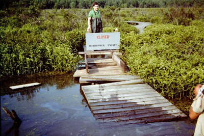 A closed sign stands next to a flooded, collapsed section of the boardwalk