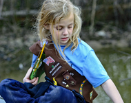 Young Brownie scout sits on boardwalk and points at a natural resource