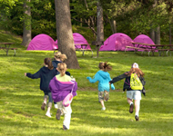 Several GIrls Scouts running across a field toward their tents