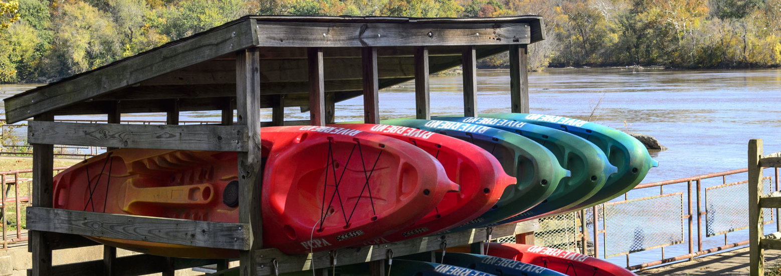 Kayaks stacked on a riverside rack