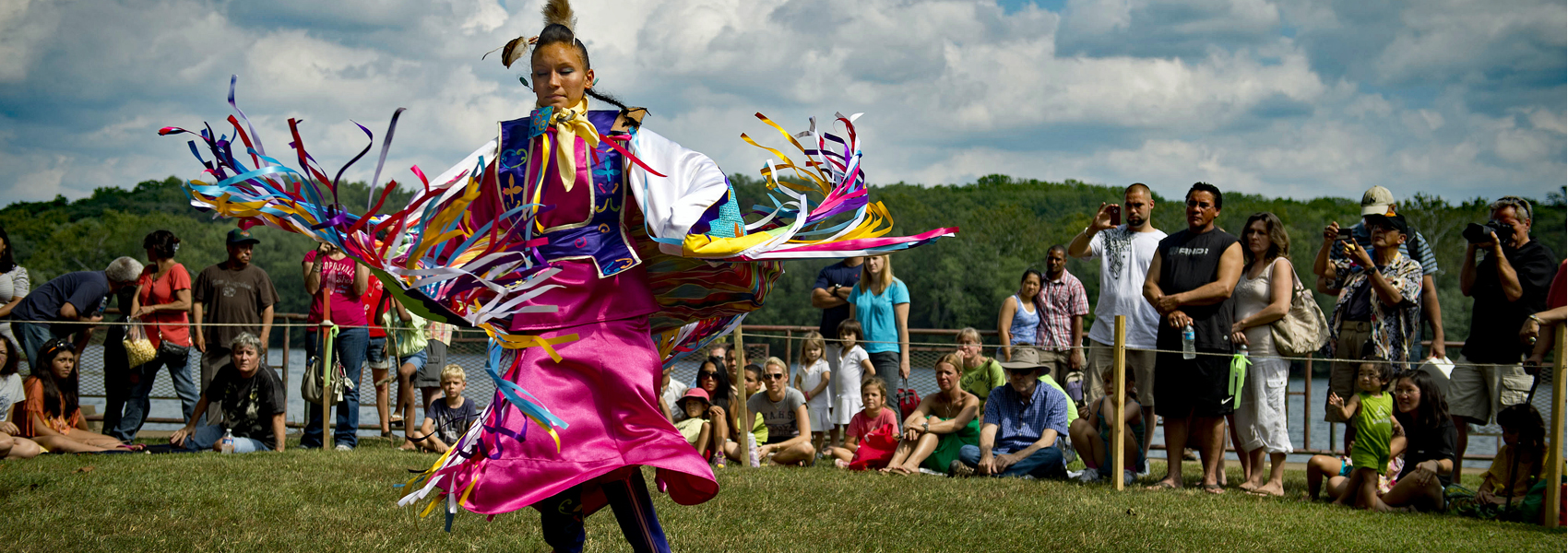 Native American in colorful costume performs a dance at Riverbend's Indian Festival