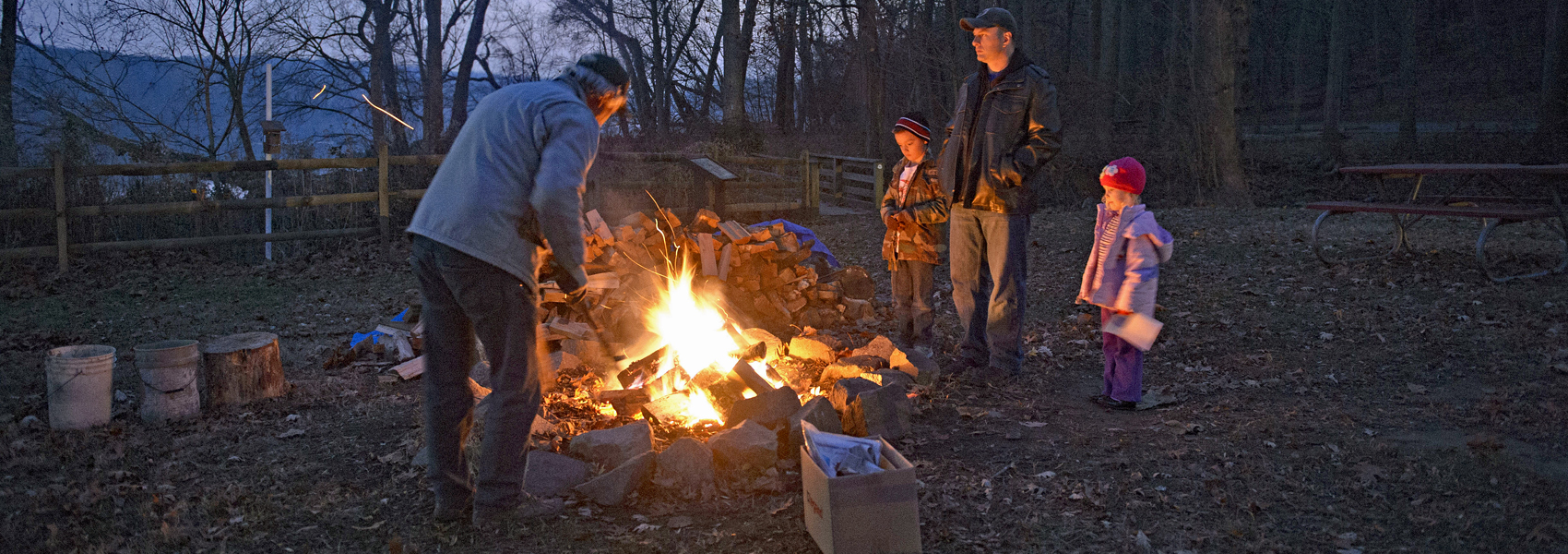 People gather round a campfire at Riverbend's Night Sky Festival