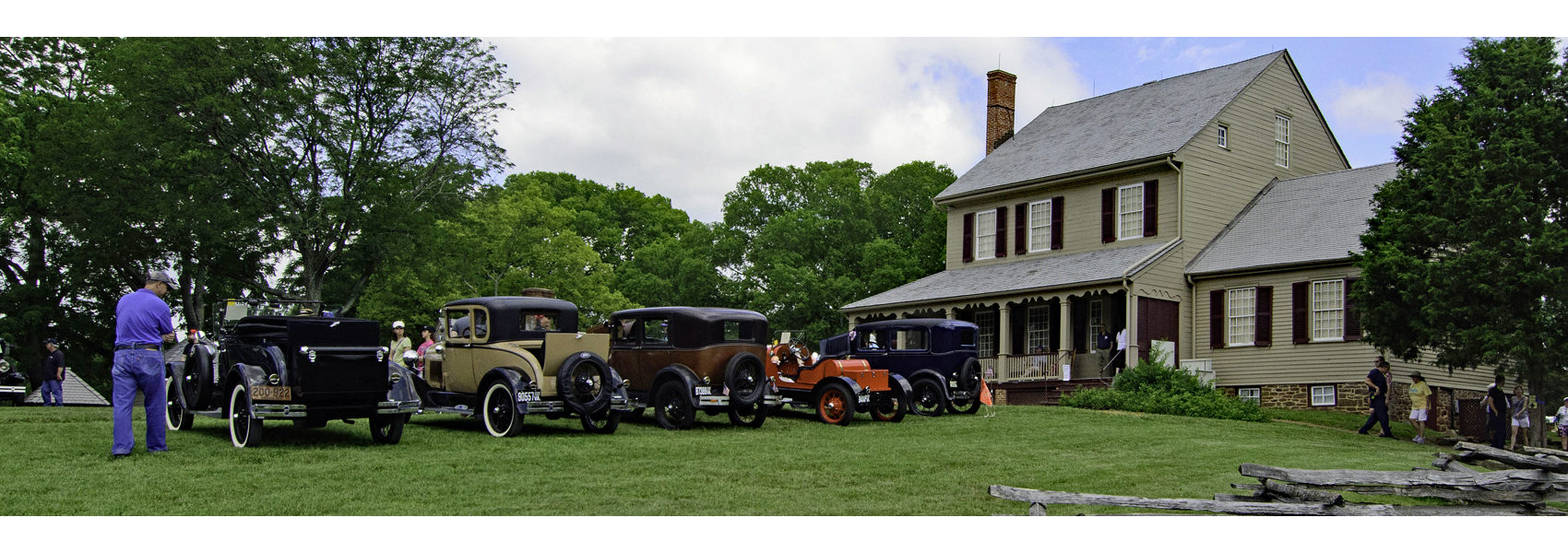 Several early 20th century cars lined up in front of Sully's historic house
