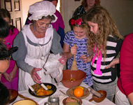 Volunteer docent in costume helps scouts mix a batter at a kitchen table