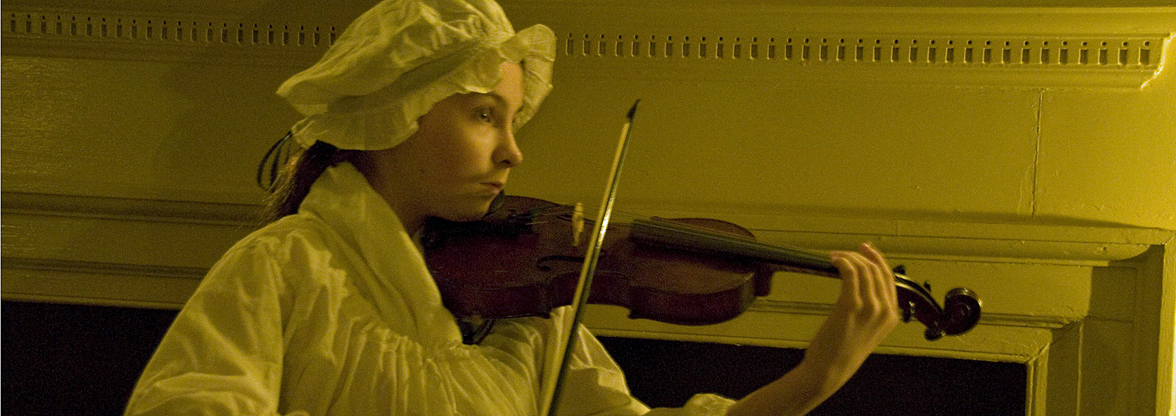 A docent in nightgown plays violin