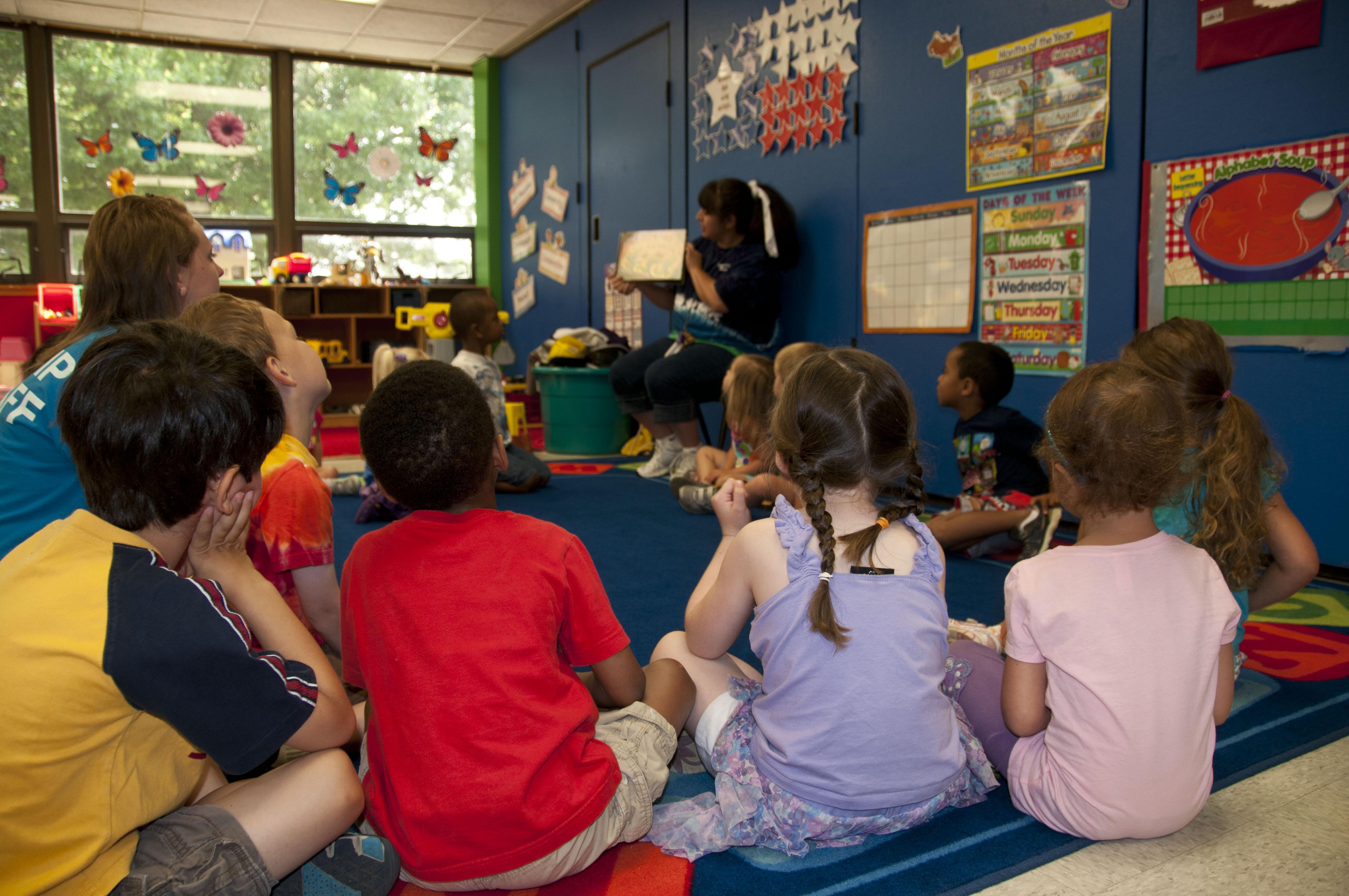 Preschool Teacher Reading A Book To Students