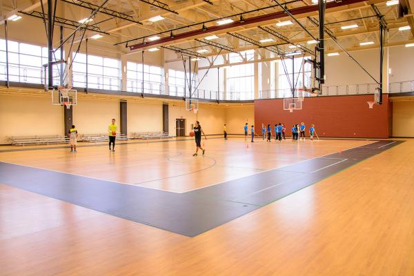 People playing basketball in gymnasium