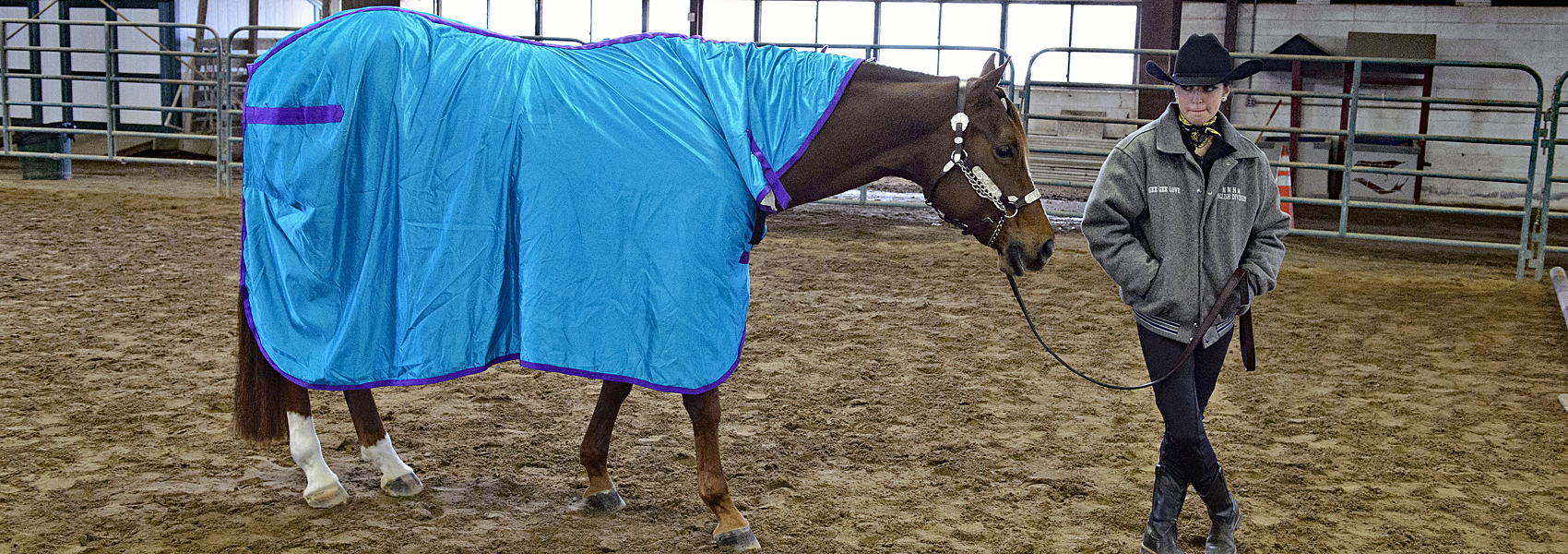 Rider stands with crossed legs next to her blanketed horse