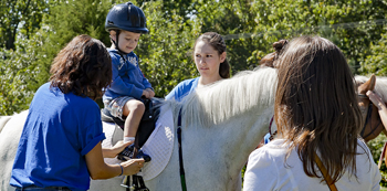 Two trainers help secure a young boy atop a horse while boy's mother looks on