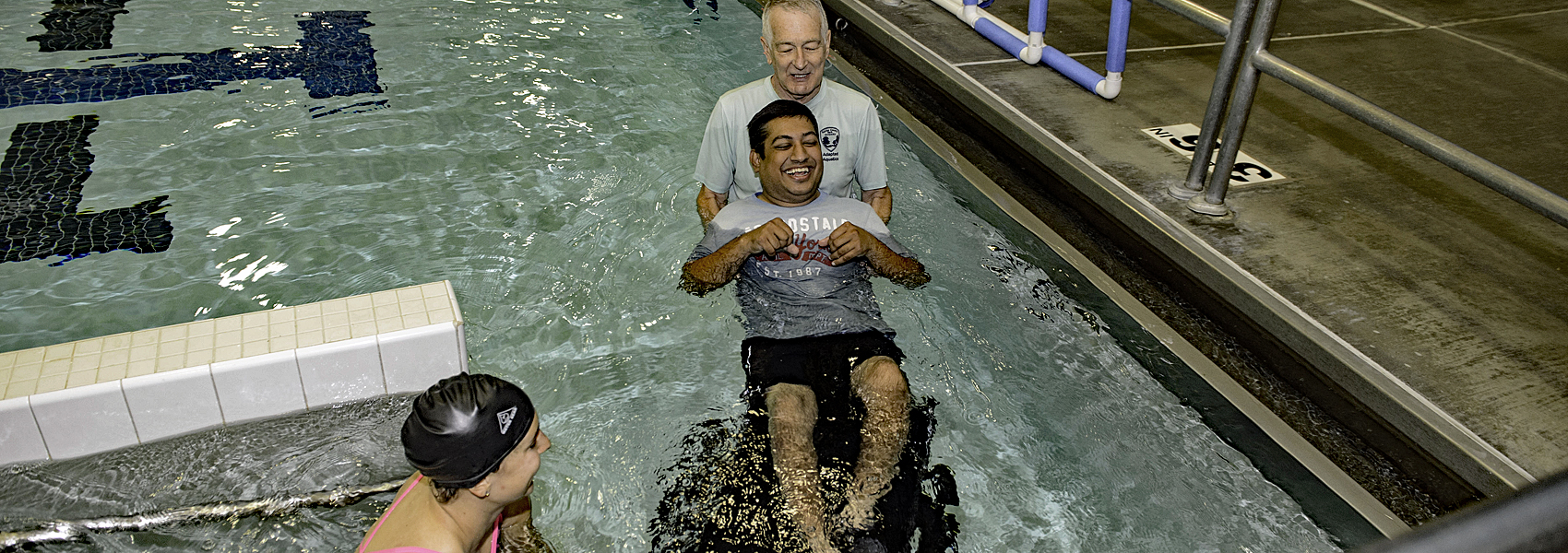 Volunteer helps swimmer in wheelchair into pool
