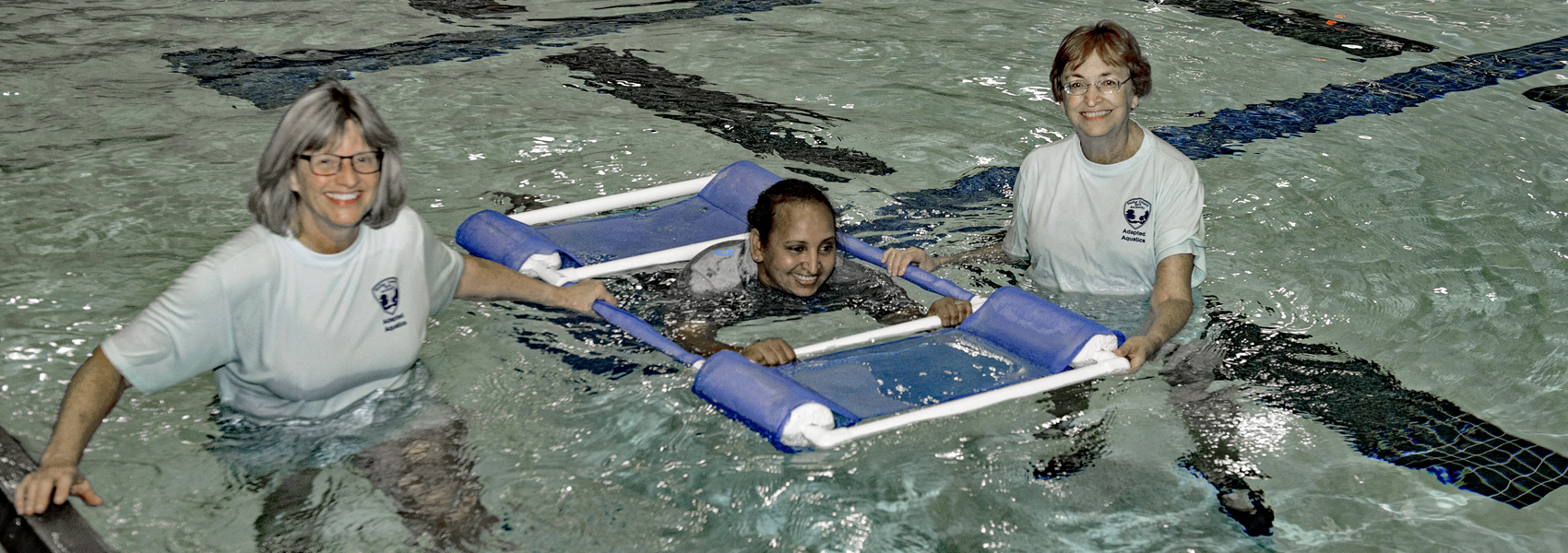 Adapted aquatics volunteers with swimmer in floating frame