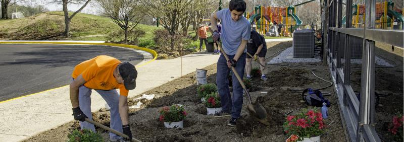 Volunteers planting bed outside RECenter