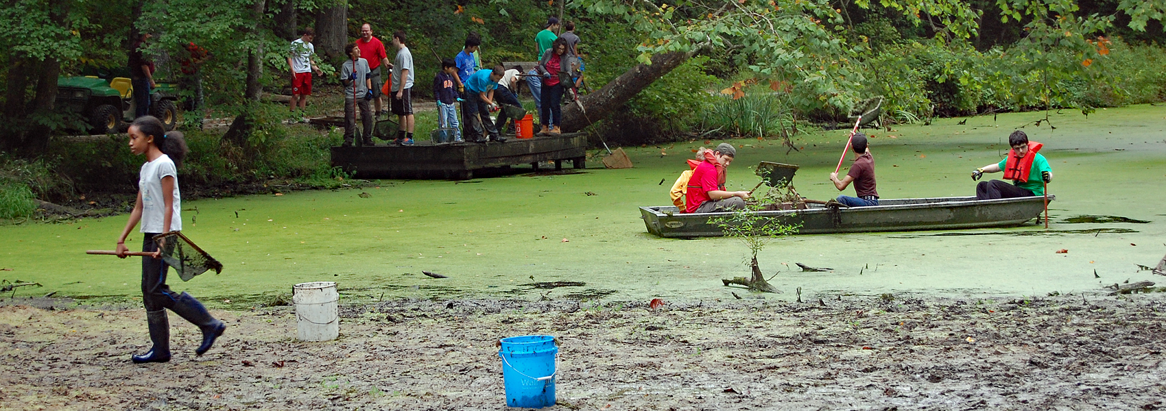 Teenagers clean duckweed from Hidden Pond
