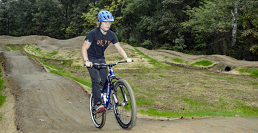 Cyclist rides up a hill on the Lake Fairfax Pump Track