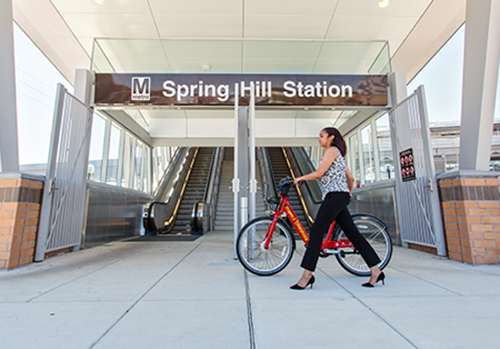 Woman with bikeshare bicycle at Spring Hill metro station