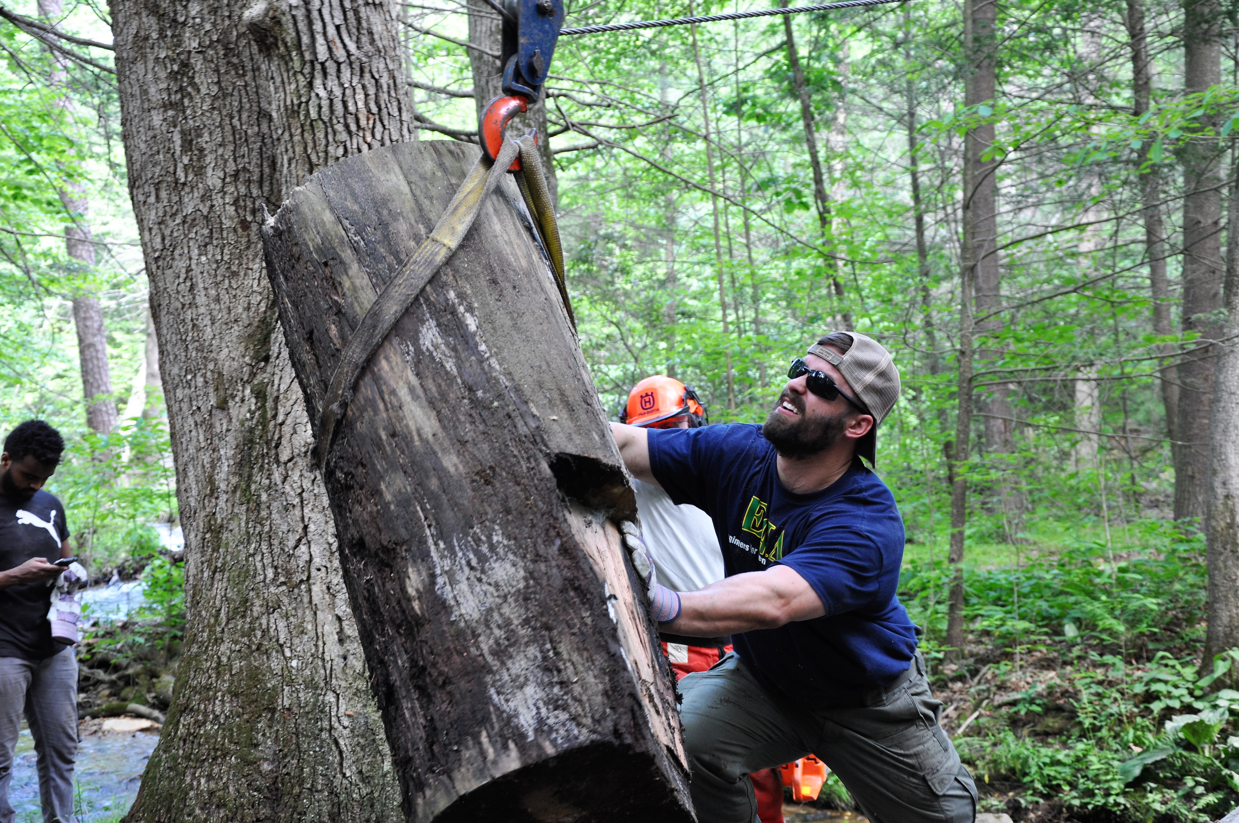 Michael Schindler moves a tree while performing trail work