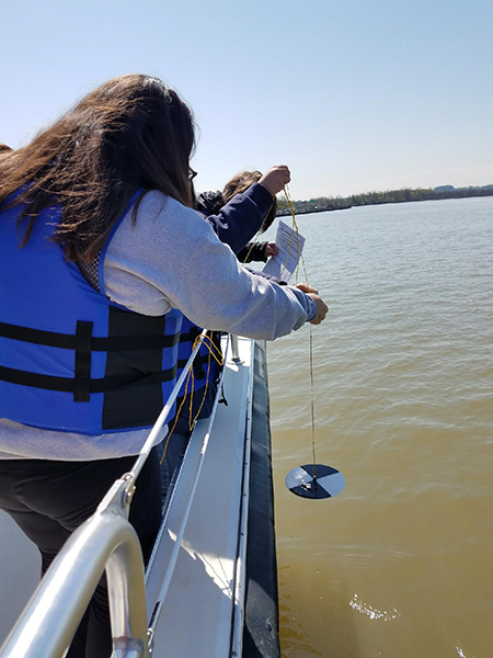 A teacher tests the turbidity of the Potomac River from the Chesapeake Bay Foundation's research boat.