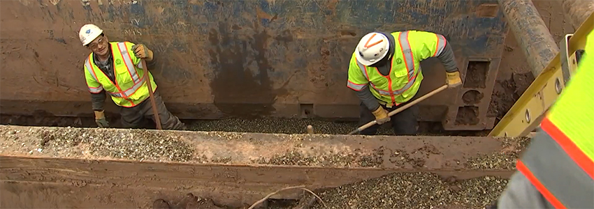 Crushed glass is placed in the trench to support a new sanitary sewer pipe.