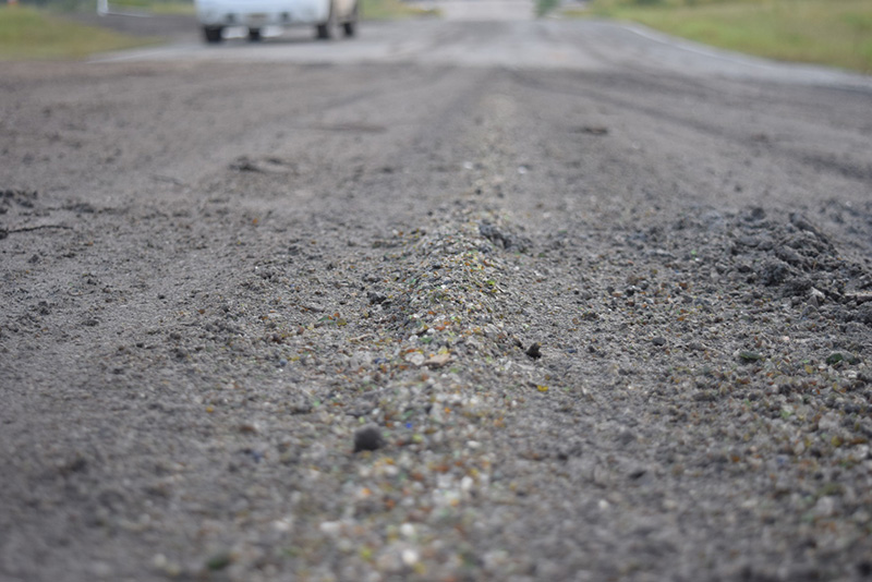 Crushed glass is visible in this repaired section of road.