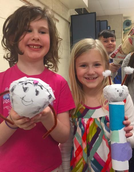 Two smiling girls hold caddisfly craft projects