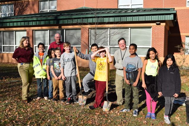 Urban foresters pose with an elementary school class after a tree planting event.
