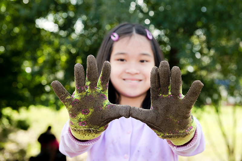 Youth with dirty gardening gloves