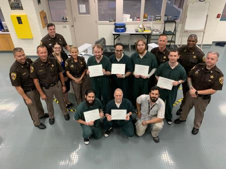 Sheriff Kincaid, staff, Nick Yacoub and inmates holding certificates