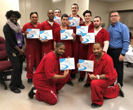 Nine kitchen crew inmates, holding certificates, are with two Aramark staff.