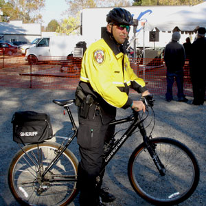 Deputy sheriff wears a helmet and is on a bicycle.