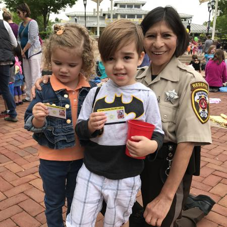 Reserve deputy sheriff with boy and girl holding child ID cards