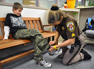 Sheriff's deputy changes transmitter battery in boy's ankle band.