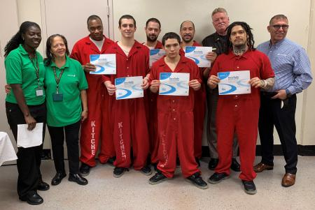 Six inmates hold their ServSafe certificates with Aramark and Sheriff's Office staff