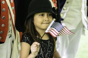 child holding USA flag at Naturalization ceremony